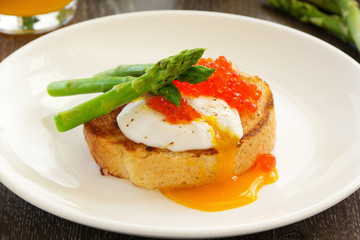 Fresh toast with poached egg, caviar and asparagus.