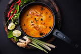 Spicy Thai soup Tom Yam with Ingredients on dark background