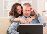 Couple using laptop at home