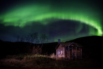 wooden cabin under northern lights