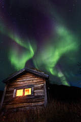 old wooden hut with northern lights