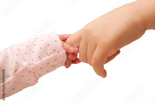 Newborn baby holding finger of older kid.