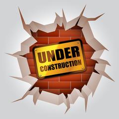 Under construction sign inside broken wall.