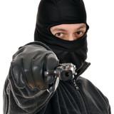 Einbrecher zielt mit Pistole