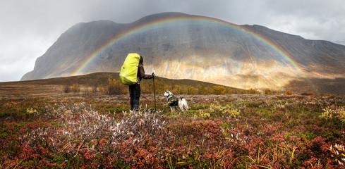 Wanderer und Hund im Herbst in Lappland mit Regenbogen