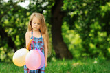 Offended little girl with baloons in a park