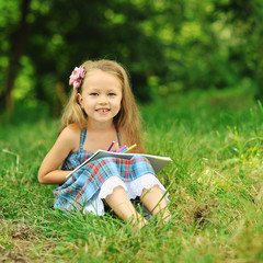 Cute little girl with pencils and note in a park