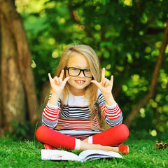 Cute little girl in with book in a park