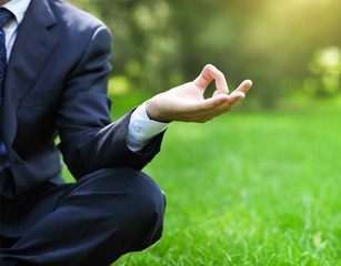 Business man relax in a park in the lotus position