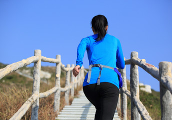 fitness woman running up at mountain stone stairs