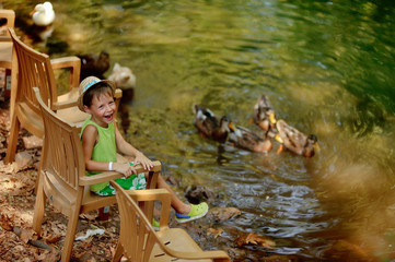 Outdoors the pond with ducks cheerful little boy in straw hat
