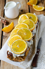 Yeast roll with poppy seeds, cream and oranges