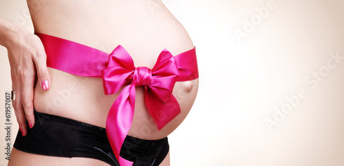 pregnant woman belly decorated with ribbon
