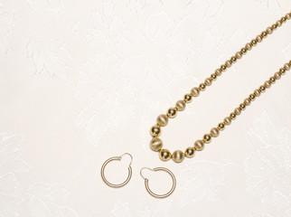 Elegant gold beads,pierced hoop earrings on beige cloth