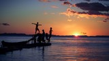 kids play on runway with sunset in the caribbean