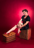 Pinup Girl in Black Dress Poses on Wooden Box