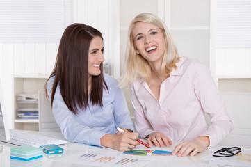Zwei junge lachende Frauen in einer Besprechung