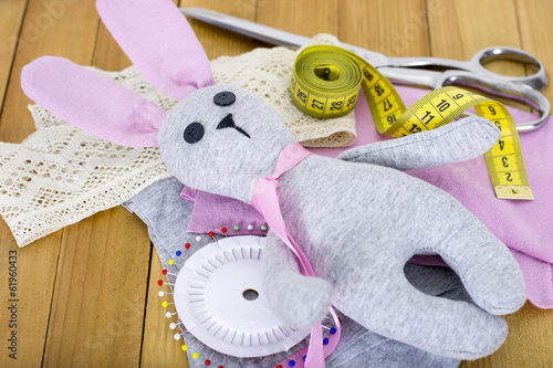 Hand made bunny toy with sewing accessories on wooden background