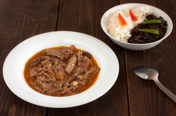 ropa vieja, on a plate with a black beans and rice