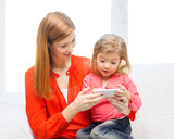 happy mother and daughter with smartphone at home