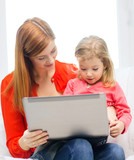 happy mother and daughter with laptop computer