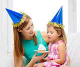 mother and daughter in blue hats with cake