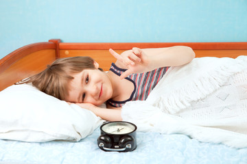 The young boy lay in bed with alarm clock