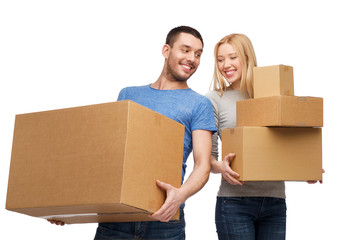 smiling couple holding cardboard boxes