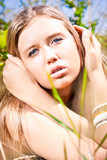 Closeup portrait of blonde woman sitting in grass