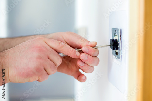 Man installing light switch with screwdriver
