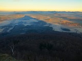 View from peak of conical mountain to morning foggy valley.