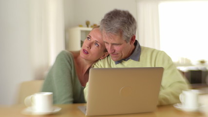 Loving couple sitting at desk with laptop