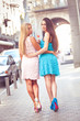 Two sexy girl in pink and blue dress walking on street