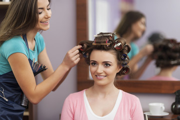 Creating trendy hairstyle by young woman