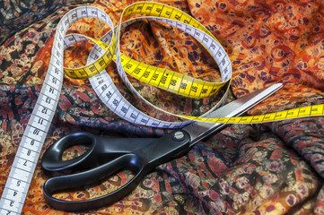Tailor measuring tape and scissors on patterned fabric