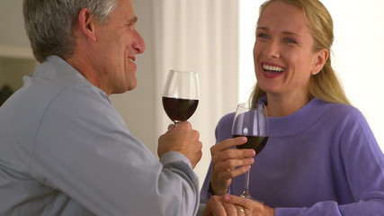 Married senior couple laughing with wine