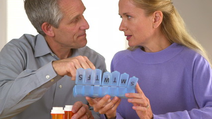 Sweet mature couple organizing pills together