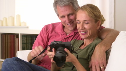 Senior couple looking at pictures on camera