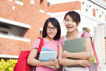 two smiling students holding books  at campus