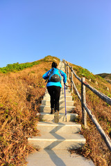hiking woman climbing stone stairs to mountain peak