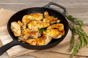 Frying pan with chicken, garlic and rosemary