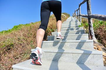 running legs on mountain stairs to peak