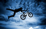 Silhouette of a man with a bmx bike.