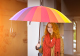 Beautiful redhead girl with umbrella in the sunshine.