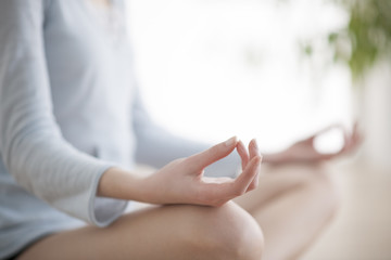 Woman meditating in the lotus position closeup