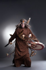 Shaman posing with tambourine, on gray background