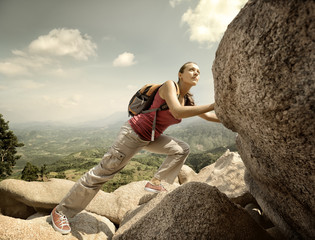Purposeful hiker with backpack crossing rocky terrain