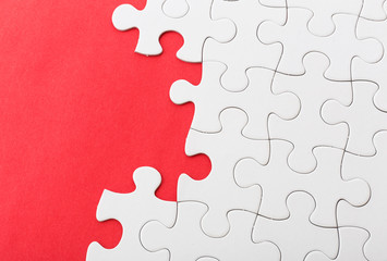 White jigsaw over red background