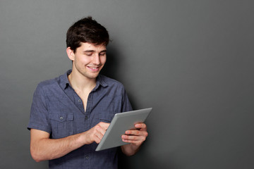 young male smiling using digital tablet