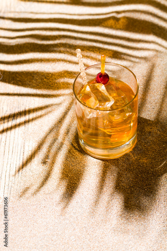 Whisky liqueur glass with ice cubes on the beach